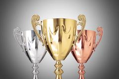 Stock Photo of close up golden,silver and bronze trophies on gray background
