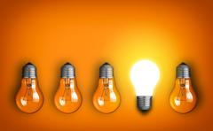 Stock Photo of idea concept with row of light bulbs and glowing bulb