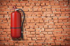 Fire extinguisher on brick wall Stock Photos