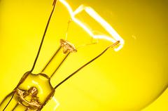 Close up glowing light bulb on yellow background Stock Photos
