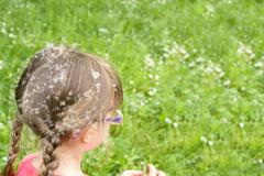 little girl sitting in the grass - stock photo