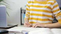 Young girl writing in her notebook, studying from textbook at home, close-up Stock Footage