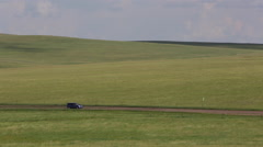 Mini van driving on an earth road through the grasslands Stock Footage