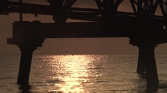 Fishing boat passes through the old rusty pier sunrise Stock Footage