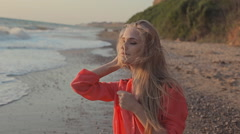 Young blond girl in red  with long hair on the beach Stock Footage