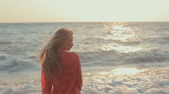 Young blond girl with long hair in red blouse on the beach Stock Footage