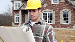Construction: home builder reads house plans and smiles to camera Stock Footage