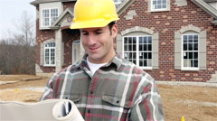 construction: home builder reads blueprints and walks off camera - stock footage