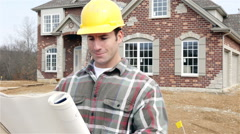 Construction: smiling home builder reads plans and looks to camera Stock Footage