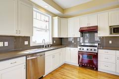 White kitchen with burgundy stove and grey counter tops Stock Photos