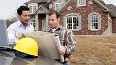 construction: architect and builder review home plan details - stock footage