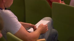 Young man student takes notes during educational or business lecture - stock footage