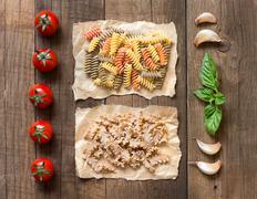 Pasta, pomodori, aglio e basilico sopra il tavolo di legno Stock Photos