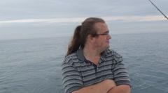 Ponytail man enjoys fishing day on boat Stock Footage