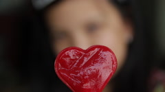 Close up Oriental young girl show heart shaped lollipop and sucks it Stock Footage