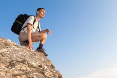 backpacker on a rock looking into the distance - stock photo