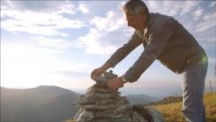 The man puts a stone on the ritual piramide - stock footage