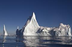 large iceberg with a few tops off the coast of antarctica - stock photo