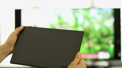 Using tablet pc in front of tv, close up HD Stock Footage