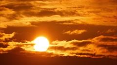 4K. Beautiful sunset sun moving across orange sky background. Timelapse Stock Footage