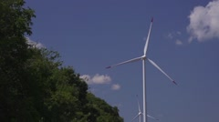 Wind turbine in a field with a small forest in slow motion Stock Footage