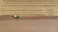 Stock Video Footage of looking down on tractor plowing a field
