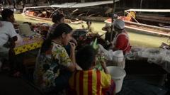 Slowed shot of people eating at the Damnoen Saduak floating market Stock Footage
