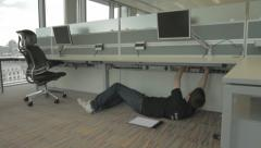 Fitting and Fixing Computer From Under Desk Stock Footage