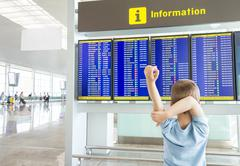 Rear view of bored kid looking panel flight times - stock photo