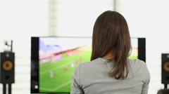 Woman watching the TV while sitting on the sofa in the living room HD Stock Footage