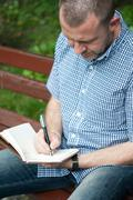 Man writing in notepad Stock Photos