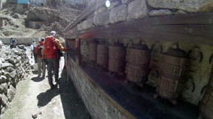 2.7K. HIMALAYAS, NEPAL - MARCH, 2014: Tourists spins a giant prayer wheel Stock Footage