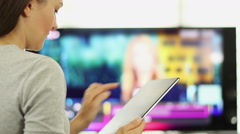 Woman using tablet pc in front of tv HD - stock footage