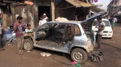 Workers group  in Mumbai street repair hammering old car Stock Footage