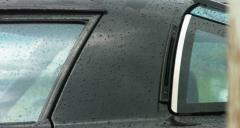 Pan Across Close Up of Black Sports Car in the Rain 4K Stock Footage