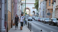 Young couple walking a dog on a busy street in an old European town Stock Footage