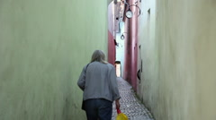 Old woman walking alone on very narrow street, Europe, medieval town Stock Footage