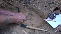 Archaeologist at a dig, hunting tools Stock Footage