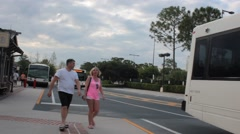 Pretty Blonde and Man Walking to Board Disney World Bus Stock Footage