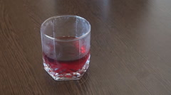 Close up hand taking glass with juice inside and full filling the glass red soda Stock Footage