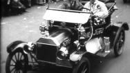 Stock Video Footage of Ford Model-T & Others Drive Through City - Vintage 8mm