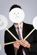 disguise: businessman hiding behind variety of masks - stock photo