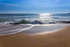 Sand sea beach and blue sky after sunrise and splash of seawater with sea foa Stock Photos