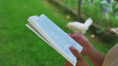 0412 Young woman hands reading a book on a country garden Stock Footage