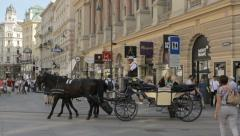 Two horse-drawn carriages crosses Graben street in the old town of Vienna Stock Footage