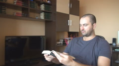 Defocused shot, student learning for school exam, reading a book in living room - stock footage