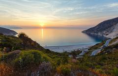 sunset on myrtos beach (greece, kefalonia, ionian sea). - stock photo