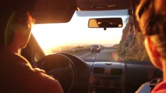 Couple driving a car in the mountains, watching sunset Stock Footage