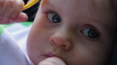 15 Close up blue eyed messy baby playing with yellow spoon Stock Footage