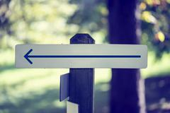 rustic wooded signboard with a left arrow - stock photo